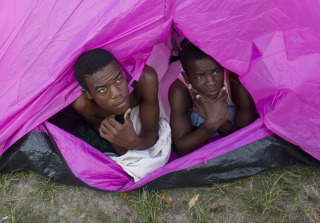 Image: Young men whose home was destroyed by Hurricane Matthew peer out of a tent in Port Salut, Haiti, Monday.