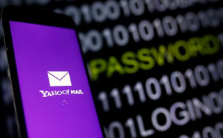 Yahoo Mail logo is displayed on a smartphone's screen in front of a code in this illustration