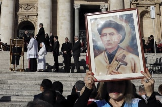 """Image: A woman holds a portrait of """"gaucho priest"""" Giuseppe Gabriele Del Rosario Brochero outside the Vatican Sunday."""