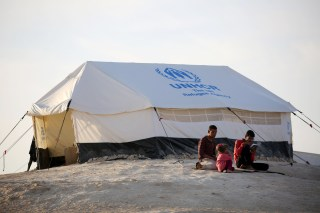 Image: Youth sit outside a UNHCR tent at a refugee camp housing Iraqi families who fled fighting in Mosul