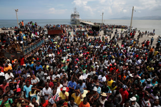 Image: People wait for relief aid to be unloaded from a Dutch navy ship after Hurricane Matthew hit Jeremie