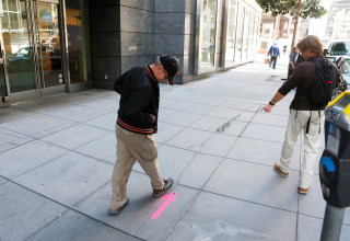 Image: Pedestrians inspect cracks near the sinking Millennium Tower in San Francisco, California