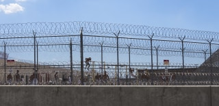 ADELANTO, CA - JULY 7, 2014: Detainees work out in the yard behind double fencing and barbed wire at