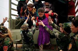 Image: Kurdish female Peshmerga soldiers help newly internally displaced children jump down from the truck upon their arrival at Al Khazar camp near Hassan Sham, east of Mosul