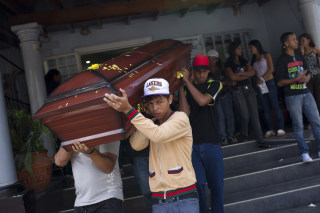 Image: Relatives of a crime victim carry his coffin during his funeral ceremony in Caracas