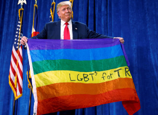 """Image: Republican presidential nominee Donald Trump holds up a rainbow flag with """"LGBT's for TRUMP"""" written on it at a campaign rally in Greeley"""