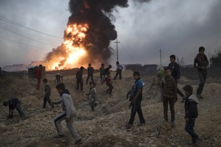 Image: Children play next to a burning oil field in Qayara, south of Mosul