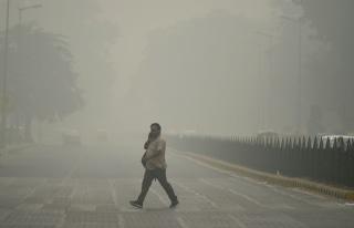 Image: An Indian pedestrian walks through heavy smog in New Delhi, Sunday.