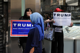 Image: A woman wearing a Muslim headscarf walks past people holding Donald Trump signs