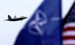 Image: NATO and U.S. flags flutter as U.S. Air Force F-22 Raptor fighter flies over the military air base in Lithuania