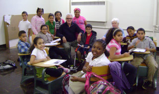 Image:  Cubs manager Joe Maddon sits with kids at the Hazleton One Community Center he helped found to improve relations in the Hazleton, Pennsylvania between whites and Hispanics