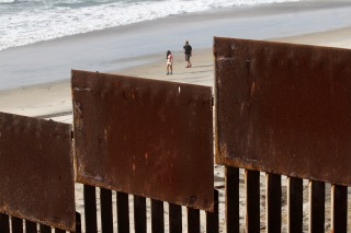 Image: Tourists are seen behind a fence separating Mexico and the United States