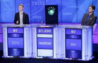 """""""Jeopardy!"""" champions Ken Jennings, left, and Brad Rutter, right, flank a prop representing Watson during a practice round of the """"Jeopardy!"""" quiz show in Yorktown Heights, N.Y. on Jan. 13, 2011. (Photo by Seth Wenig/AP)"""