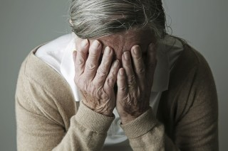 Image: Elderly woman covering face with her hands