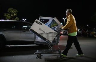 Image: Shoppers exits a Best Buy after purchasing electronic items during Black Friday sales in San Diego