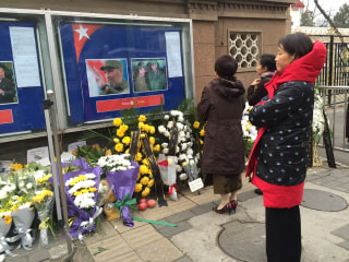 Image: Women stand at a memorial for Fidel Castro at the Cuban embassy in Beijing