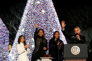 Image: Obama, joined by the first lady, their daughter Sasha and Longoria, reacts after pressing a button to light the National Christmas Tree in Washington