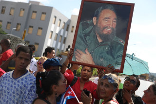 Image: Crowds hold pictures of Fidel Castro as they await the convoy of vehicles escorting his remains near the Moncada Barracks on Saturday.