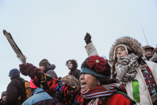 """Image: A woman from the Tlingit Tsimphean tribe holds an eagle feather into the air in Oceti Sakowin camp as """"water protectors"""" continue to demonstrate against plans to pass the Dakota Access pipeline near the Standing Rock Indian Reservation, near Cannon"""