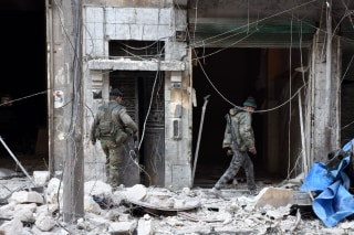 Image: Pro-government forces inspect a building in eastern Aleppo Sunday after retaking it from rebel fighters.