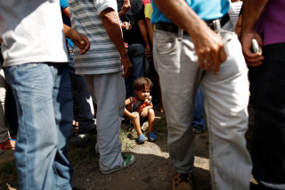 Image: Emmanuel Cuauro seats on the sidewalk next to his mother Zulay Pulgar, as they make a line outside the hardware store to buy cement and re-sell it in Punto Fijo