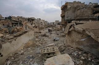 Image: Syrians walks down a destroyed street in Aleppo's al-Akroub neighbourhood on Dec. 17.