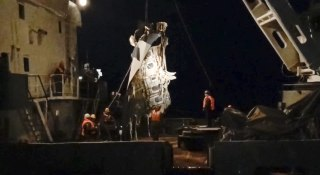 Image: Rescuers lift a fragment of a plane