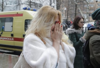 Image: A mourner covers her face near a temporary shrine outside the home stage of the Alexandrov Ensemble, or Red Army Choir, in Moscow.