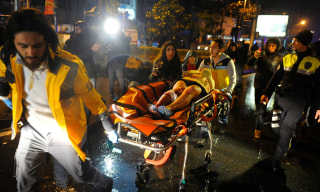 Image: An injured woman is carried to an ambulance from a nightclub where a gun attack took place during a New Year party in Istanbul
