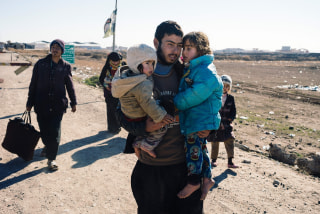 Image: An Iraqi man carries his children near the town of Bartella as people return to their liberated neighbourhoods in eastern Mosul, Saturday.