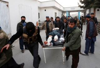 Image: Men carry an injured police officer to a hospital after a suicide attack in Kabul