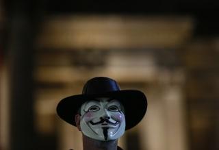 Image: A supporters of the activist group Anonymous wears a mask during a protest in London, Britain.