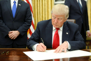 Image: President Donald Trump signs his first executive orders in the Oval Office in Washington, D.C. on Jan. 20.