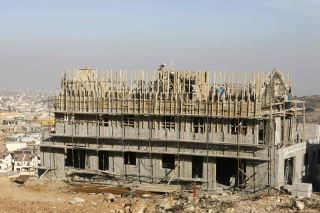 Image: Palestinian laborers work at the construction site of a new housing project in the northern part of the Israeli settlement of Efra