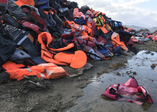 Image: A little pink life jacket lies in a giant dump of thousands of life jackets
