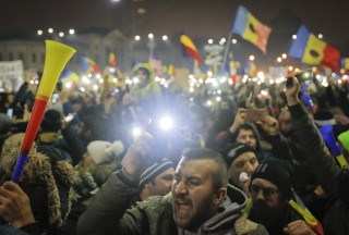 Image: Tens of thousands shine lights from mobile phones and torches during a protest in front of the government building in Bucharest, Romania.