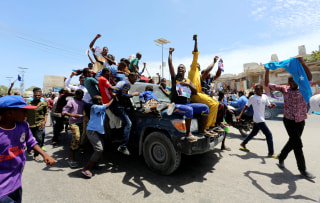 Image: Civilians ride on a police car as they celebrate the election of President Mohamed Abdullahi Mohamed, Thursday.hu