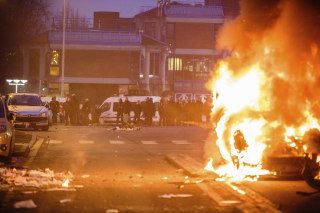 Image: Police face protesters as a car burns in Bobigny, Paris, Saturday.