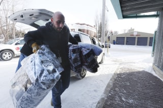 Image: A person brings blankets into a community hall for refugees