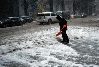 Image: A man shovels snow from a street during a winter storm in New York