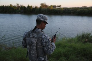Image: A Texas National Guard soldier checks his radio while monitoring the U.S.-Mexico border in 2014