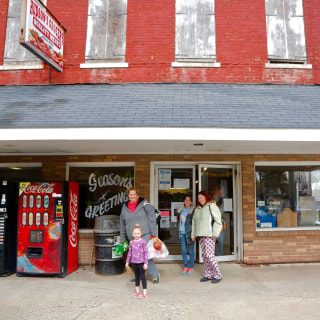 Image: Shoppers in Wayntown, Indiana, leave the town's only grocery store, Hudson's Grocery, while President Trump engages with reporters at a press conference in Washington, D.C., last week.