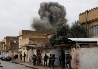 Image: Iraqi policemen walk during an airstrike against ISIS militants in Mosul