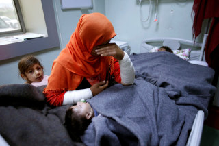 Image: A mother reacts as her daughter Ranmea is treated for possible exposure to chemical weapons agents in a hospital west of Erbil in Mosul