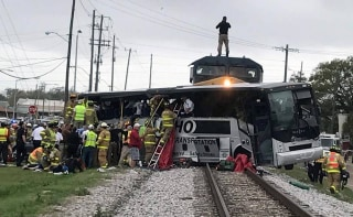 Image: Biloxi firefighters help passengers of a charter bus out after the bus collided with a train in Biloxi