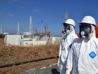 Image: Workers stand in front of the stricken Fukushima Daiichi nuclear power plan