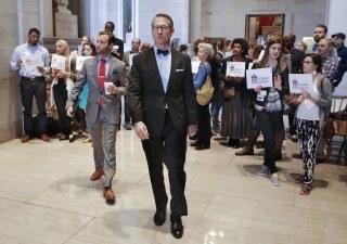 Image: Sen. Bo Watson, center, R-Hixson, walks past demonstrators opposed to immigration restrictions