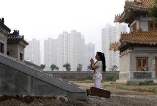 Image: A woman prays in Tianjin