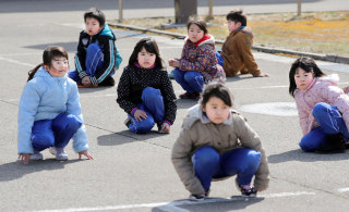 Image: Elementary school students crouch during an evacuation drill