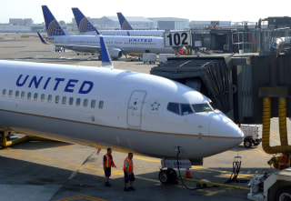 Image: A United Airlines airplane sits at a gate.